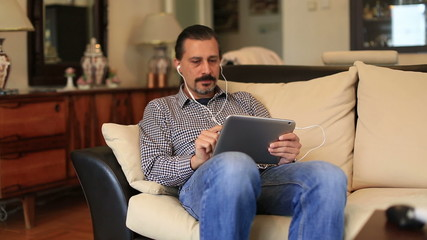 man sitting sofa and listening music with tablet