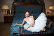 Ballerina lying down on bed and daydreaming in luxury interior