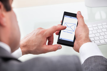 Businessman Holding Mobile With New Message On A Screen