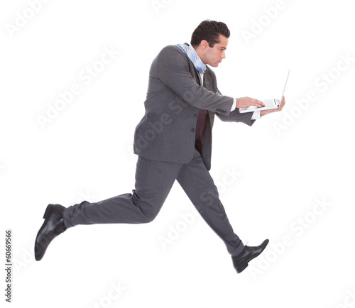 Businessman Using Laptop While Running