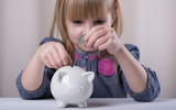 Child putting coin into piggy bank.