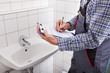 Plumber Standing In Front Of Washbasin Writing On Clipboard