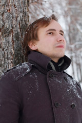 Young man with snowflakes in hair stands near tree and looks up
