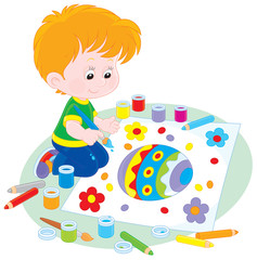 Little boy drawing a colorfully decorated Easter egg