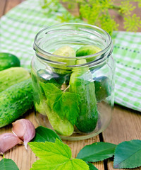 Cucumbers in a jar with leaves and napkin