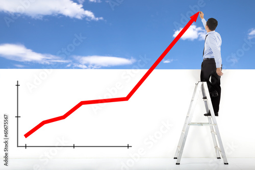 businessman standing on ladder drawing global diagrams