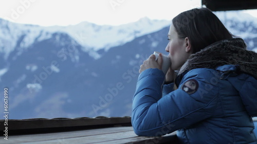 Beautiful girl drinking hot tea in the mountains