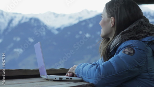Woman with laptop looking at beautiful view in the mountains