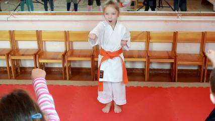 Karate kick girl in kimono beat in front of children