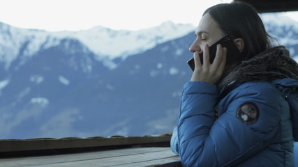 Attractive woman talking on cellphone in the mountains