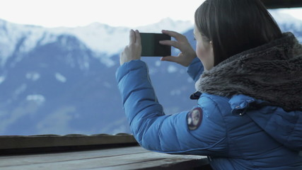 Young woman taking photograph by cellphone in the mountains