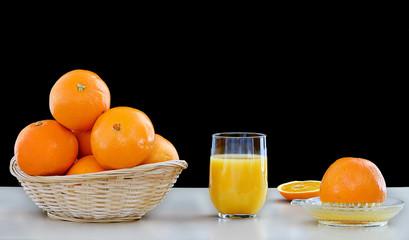 panier d'oranges et jus pressé dans un verre