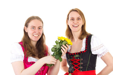 Beautiful and happy women in dirndl with bunch of roses