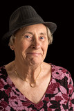 Senior lady wearin a fedora with an amused look on her face