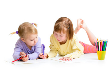 two girls drawing with color pencils together over white backgro