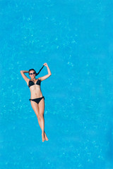 Woman floating above pool water