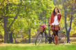Beautiful young female posing in park with a bicycle