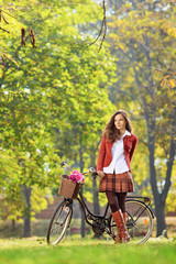 Beautiful female in park with her bicycle