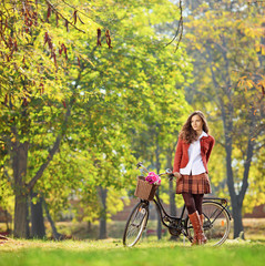 Beautiful young woman posing in park with her bicycle
