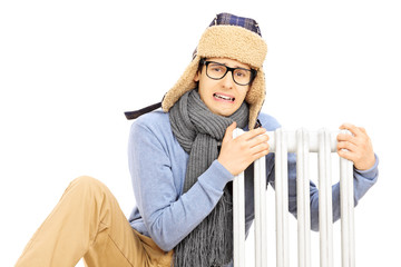 Chilled young man with winter hat sitting next to a radiator