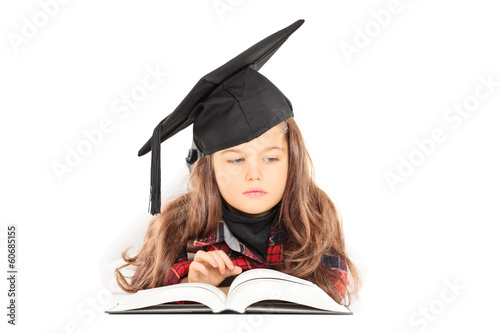 Cute little girl with graduation hat reading a book