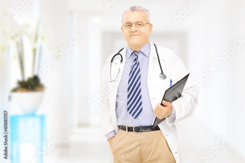 Confident middle aged doctor holding a clipboard in a hospital