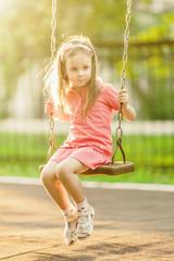 Pretty little girl swinging on seesaw beneath bright shining