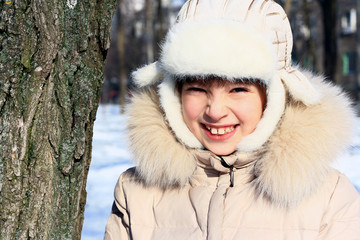 Little girl in winter fur clothing plays outdoors in the winter.