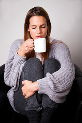 Young woman sitting in a chair drinking a hot drink