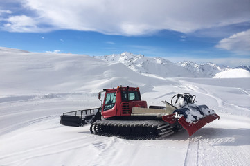 Modern red snow groomer in a sunny day