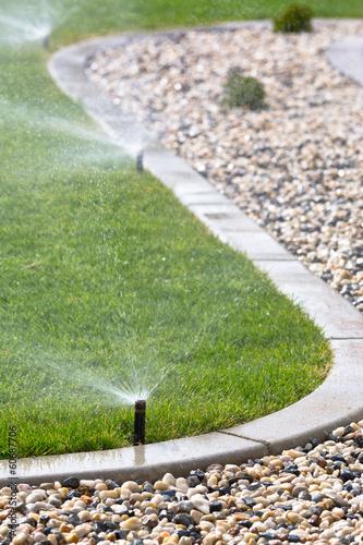 Sprinklers watering grass - 60687706
