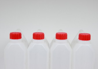 Four empty jerrycans of white plastic with red lids
