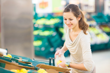 Pretty, young woman shopping for fruits and vegetables in produc
