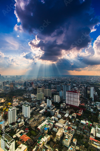 Rays of light shining through dark clouds with city below