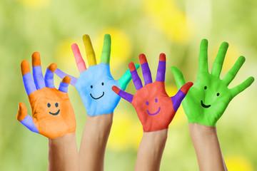 bemalte Hände vor grünen Hintergrund
