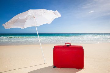 red suitcase under a white sunshade