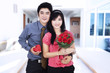 Attractive couple holds a gift and flowers