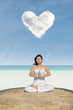 Asian woman meditating at beach under love cloud