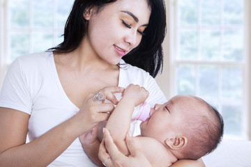 Asian mother feeding her baby at home