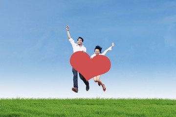 Asian couple jumping on grass with heart card