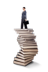 Businesswoman standing on a stack of books