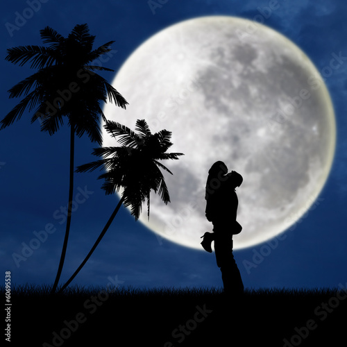 Couple hugging under full moon at beach