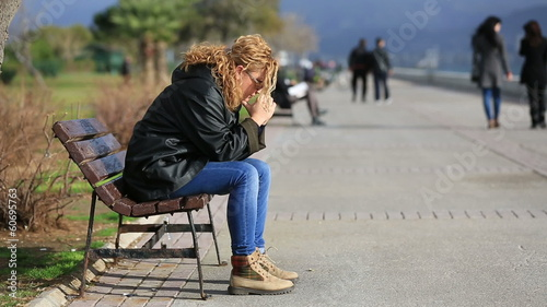 lonely blonde women sitting a bank and looking arround