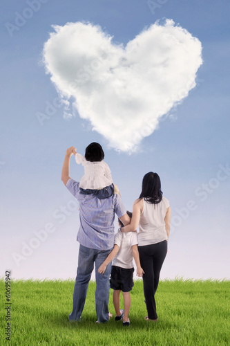 Family looking at heart clouds