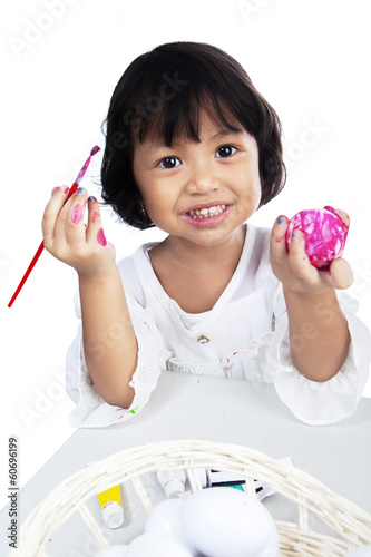 Cute little girl coloring an easter egg