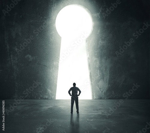 Businessman  looking through key hole