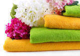Colorful towels and flowers, isolated on white