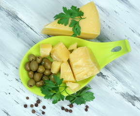 Parmesan cheese, fresh herbs and olives on wooden background
