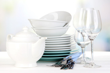 Clean dishes on table on bright background