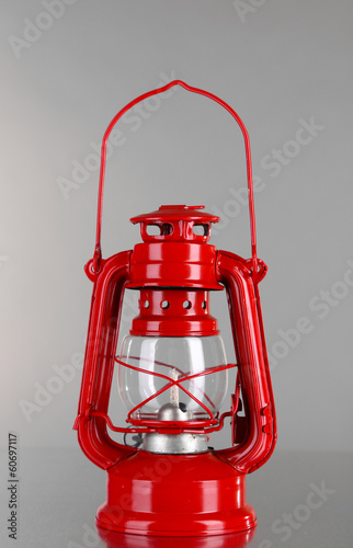 Red kerosene lamp on grey background
